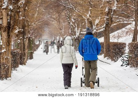 People in winter walk in the Park. Young parents with a baby stroller. Snow