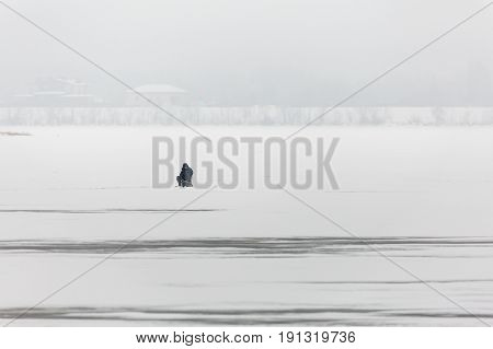 Winter fishing on the Volga river in Saratov. On the horizon is the city of Engels. Russia