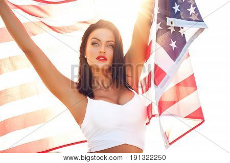 Sexy young woman holding star spangled banner USA flag 4th of July Independence day