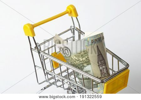 Metallic shopping trolley fragment with ten rubles over white background