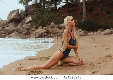 Bikini model girl posing sexy at tropical beach location. Vogue style