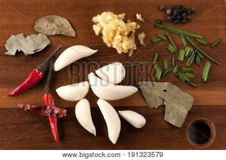 Garlic peppers, and spices for cooking. An overview image of assorted vegetables and spices on a cutting board to be used in cooking.