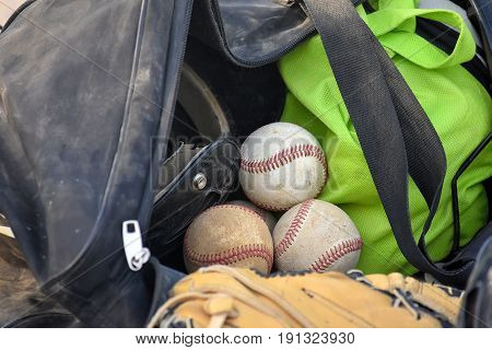 baseballs and sports glove in coach's duffel bag with helmet