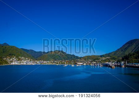 SOUTH ISLAND, NEW ZEALAND- MAY 25, 2017: Gorgeous coast zone of the city in the horizont from ferry between north and south island in New Zealand, sailing into Picton.