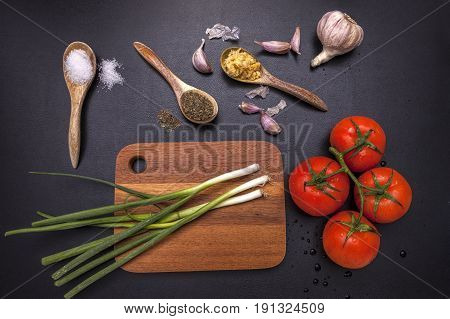 Assorted veggies on and around a cutting board that make up ingredients for cooking.