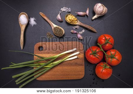 Veggies and spices around a cutting board for cooking.