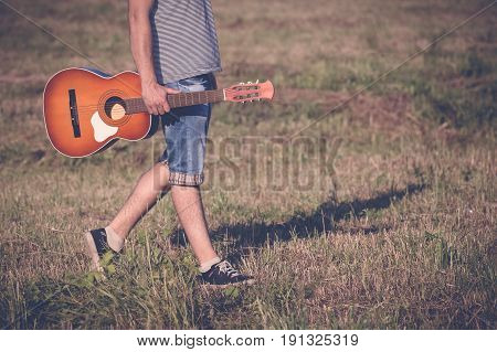 Fashionable guy with acoustic guitar walking in nature