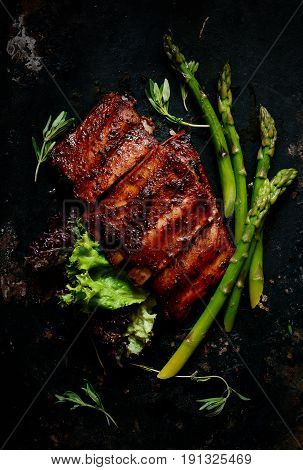 Spicy pork ribs barbecue with green salad and asparagus on a dark background