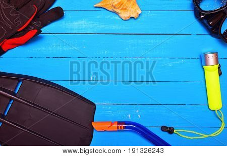 Equipment for scuba diving on a blue wooden background empty space in the middle