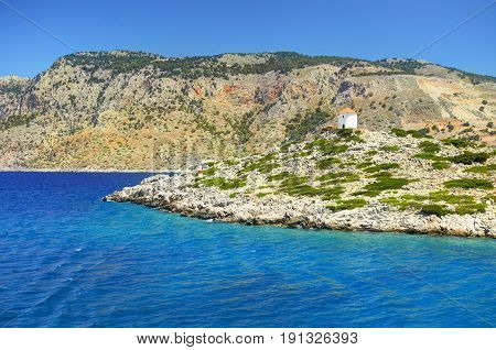 Beautiful view on Symi island stone rocks white mill flouring-mill with orange roof on green hill. Blue crystal clear water of Aegean sea, stone and sand beach, stone rocks. Rhodes island tours