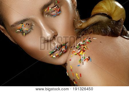 Beautiful pretty woman with natural light makeup with snail. Cosmetology therapy. NATURAL BEAUTY CONCEPT. Fashion portrait with cute girl and snail on black background. Snail girl. Nude.