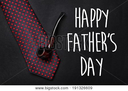 Happy Father's Day Text Sign. Fathers Day Greeting Card. Classic Tie With Wooden Tobacco Pipe On Bla