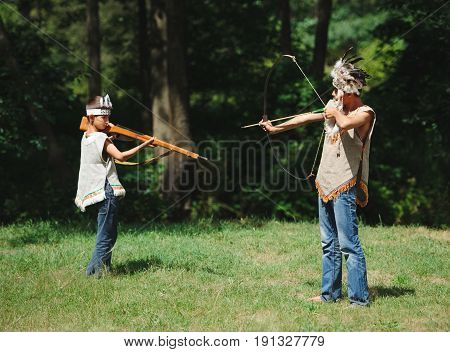 Photo of little funny boy playing native american