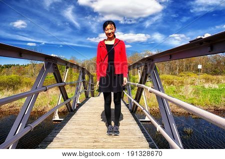 A Chinese woman standing on a boardwalk through a wetland ecosystem at white memorial conservation center in Litchfield Connecticut on a beautiful spring day.