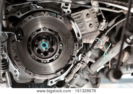 Detail of lifted automobile at repair service station. transmission