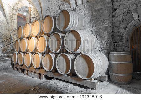 Ornate wine barrels in a cool castle cellar