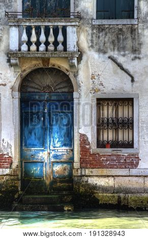 A blue door on a canal in Venice, Italy.