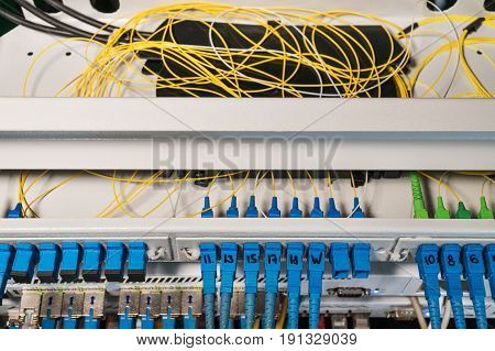 Rack with routers with open top cover and wires inside