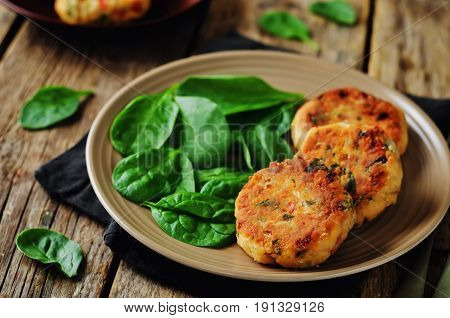 Salmon fritters with spinach on a dark wood background