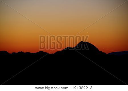 The warm colors of the evening sky with a mountian silhouetted against it.