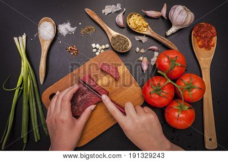 Cutting raw steak for cooking. An overhead photo of a person cutting a piece of raw steak by vegetables and other ingredients.