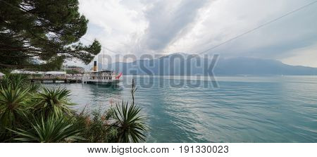 Atmospheric Lake Leman Swiss vista with a paddle steamer boat in dock