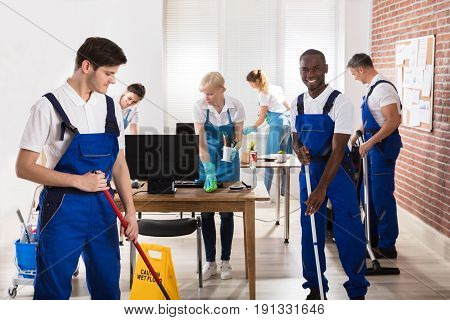 Group Of Diverse Janitors In Uniform Cleaning The Office With Cleaning Equipments