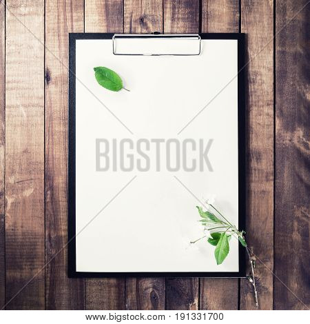 Photo of clipboard with blank letterhead cherry blossoms with green leaves on vintage wooden background. Template for placing your design. Top view.