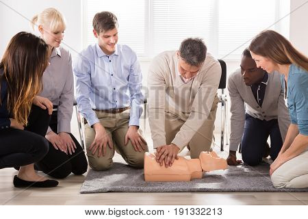 The Students Are Looking At The Instructor Performing Resuscitation Technique On Dummy poster
