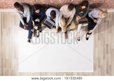 Overhead View Of Diverse People Sitting On Hardwood Floor Looking At Blank Paper