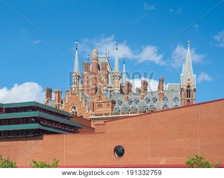 Outside view of the British Library building, national library of the UK in London, with the gothic towers of St Pancras Station behind the wall.