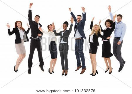 Excited Businesspeople Raising Their Hands While Jumping On White Background