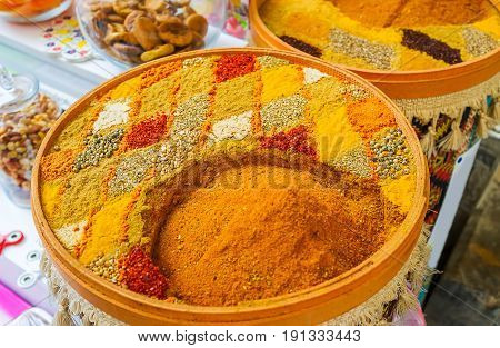 The mix of fragrant spices on the plate decorated with patterns created of pepper saffron curcuma other powders herbs and seeds Antalya Turkey.