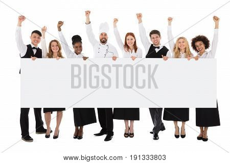 Portrait Of Multiracial Restaurant Staff Holding Billboard Raising Their Arms