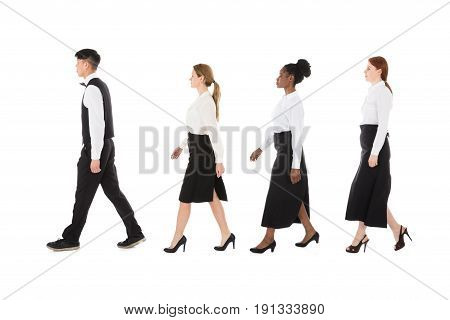 Young Restaurant Staff Walking In Row Against White Background