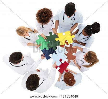High Angle View Of Medical Team Solving Jigsaw Puzzle