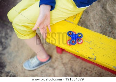 School Girl Playing With Fidget Spinner On The Playground. Popular Stress-relieving Toy For School K