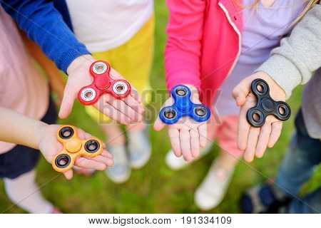 Four School Children Playing With Fidget Spinners On The Playground. Popular Stress-relieving Toy Fo