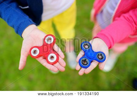Two School Children Playing With Fidget Spinners On The Playground. Popular Stress-relieving Toy For