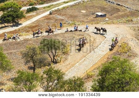 View on donkey traveling tourists on pathway road. Donkey road serpentine road sideway. Travel on donkey animal transport. Greece island Lindos city. Travel on donkey to acropolis