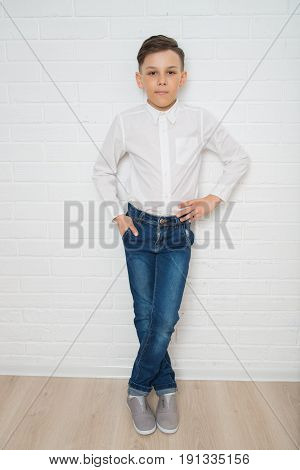 Thoughtful boy in white shirt and jeans standing against a white brick wall.