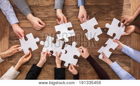 High Angle View Of Businesspeople Hand Solving Jigsaw Puzzle
