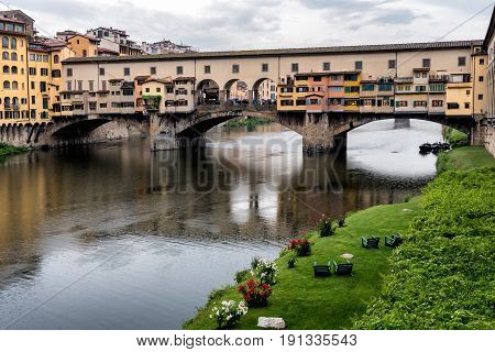 Ponte Vecchio, famous old bridge in Florence on the Arno river, Firenze, Tuscany, Italy - on a dramatic cloudy day