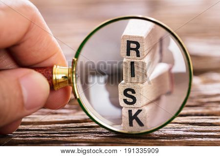 Close-up Of A Person Inspecting Risk Block With Magnifying Glass On Wooden Table