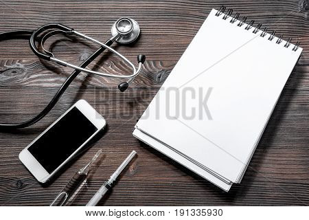 Make an appointment with doctor by phone dark wooden desk top view composition with notebook, syringe, ampoule.