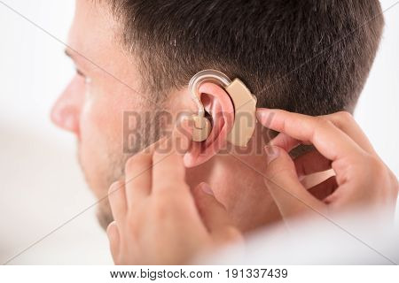 Close-up Of A Person Putting Hearing Aid On Man's Ear
