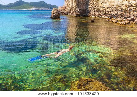 Woman bikini snorkeling around scenic Methoni Castle, a medieval fortification in Methoni, Messenia, Peloponnese, Greece. Female snorkeler swims in crystal water. Summer watersport activity leisure.