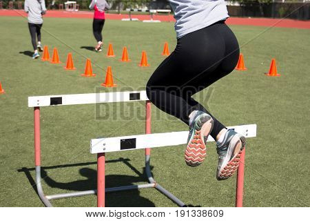 A female athlete jumping over track hurdles during track and field practice