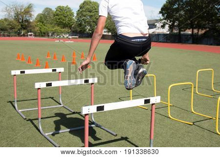 A high school male athlete bounding and jumping over hurdles and orange cones on a green turf field