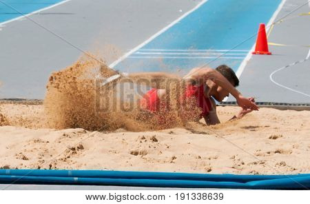 A long jumper triple jumper landing in a sand pit during a track and field competition.